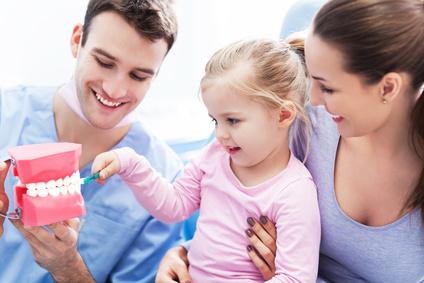 Zahnarzt bringt Kind das Zähneputzen bei
